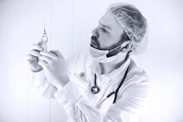 白衣と古い注射器でひげを生やした医者の白黒写真