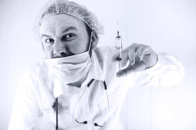 흰 코트와 오래된 주사기에 수염 난 의사의 흑백 사진