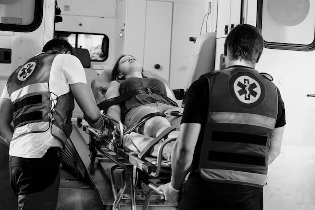 Черно-белое фото молодой женщины, пострадавшей в аварии, лежит на носилках в машине скорой помощи
