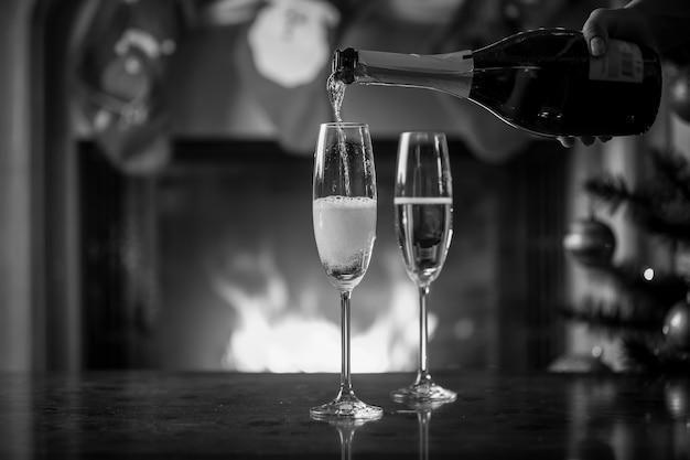 크리스마스 테이블에 샴페인으로 잔을 채우고 병을 들고 있는 손의 흑백 사진