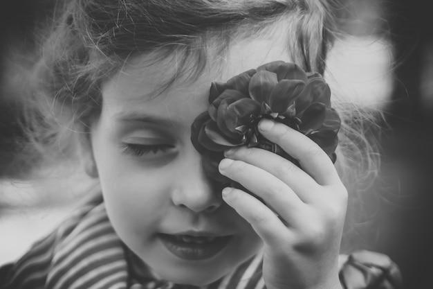 빨간 조지나 또는 달리아로 눈을 덮고 있는 어린 소녀의 흑백 사진. 순수한 피부와 미소를 가진 아름다운 젊은 여성이 꽃을 가지고 놀고 그것으로 그녀의 얼굴을 만지고 있습니다.