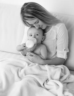 침대에서 아기에게 먹이를 주는 어머니의 흑백 사진