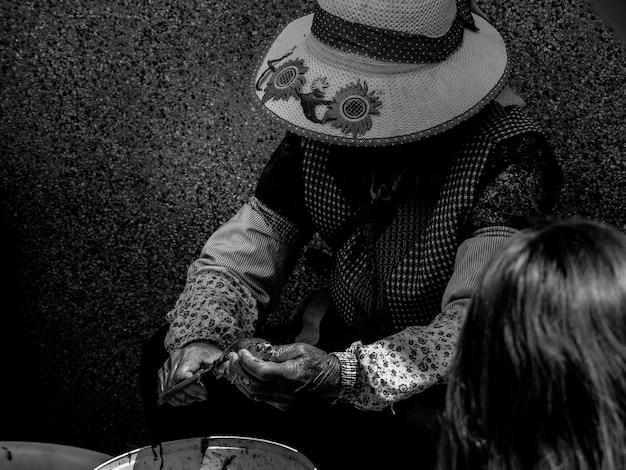 帽子をかぶっている老婆の黒と白の写真