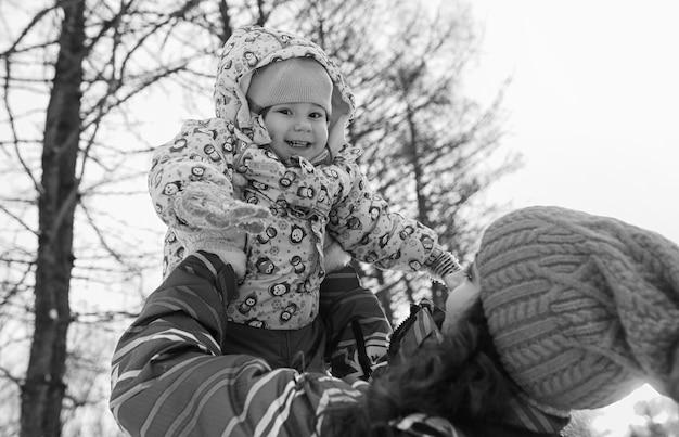 Черно-белое фото родителей, держащих ребенка на руках в зимнем парке