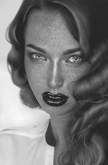 カメラを見ているそばかすを持つ魅惑的な女の子の白黒写真