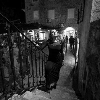 夜の街の階段を上るセクシーな女性の白黒写真