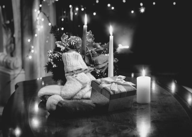 크리스마스 양초, 선물, 양말로 장식된 탁자의 흑백 사진