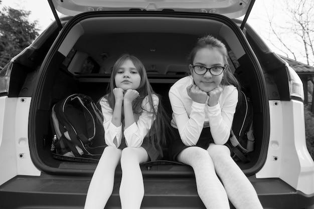 열린 차 트렁크에 앉아 웃는 두 여학생의 흑백 사진