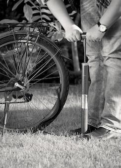 수동 펌프로 자전거 타이어를 펌핑하는 젊은 남자의 흑백 사진
