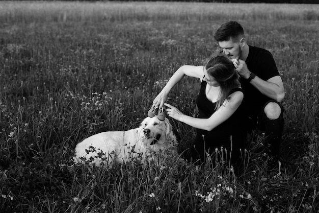 강아지와 산책에 탐닉하고 머리에 어린이 신발을 신고 있는 젊은 임신한 부부의 흑백 사진. 근심없고 행복합니다. 아이를 기다리고 있습니다. 임신. 좋은 순간들.