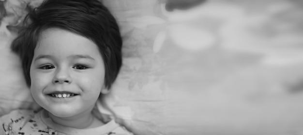 베개에 누워 있는 어린 아이의 흑백 사진 초상화