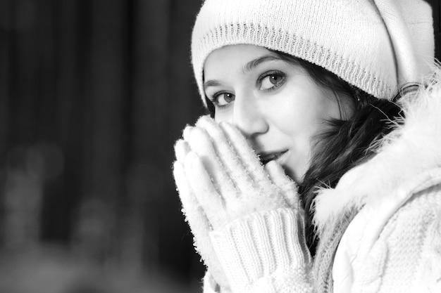 Черно-белый фотопортрет девушки в зимнем пальто, шапке и перчатках