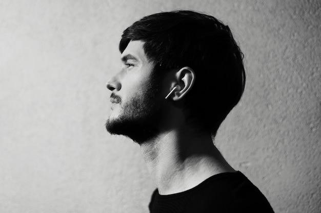 テクスチャ背景に耳にワイヤレスイヤホンを持っている若い男の黒と白の写真の側面の肖像画。