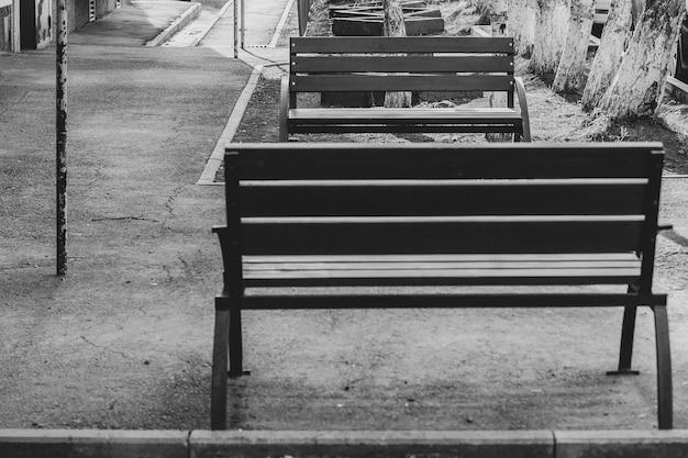 コロナウイルスcovidの検疫中に家の中庭に空のベンチと白黒写真
