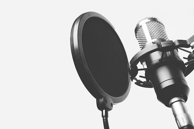 スタジオで歌っているマイク録音の白黒写真