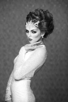 Черно-белое фото модели невесты с современной свадебной прической, аксессуарами и свадебным платьем