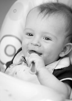 スプーンを保持している生後9ヶ月の男の子の黒と白の肖像画