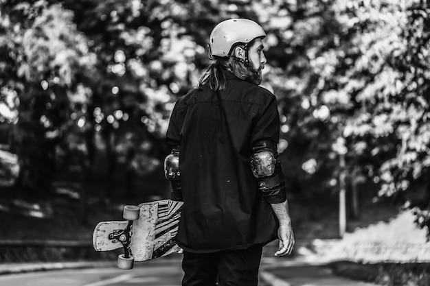 Черно-белый портрет бородатого парня, держащего скейтборд, лонгборд. фото высокого качества