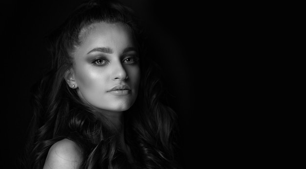 スタジオで影でポーズをとる輝かしい若い女性の黒と白の肖像画。空きスペース