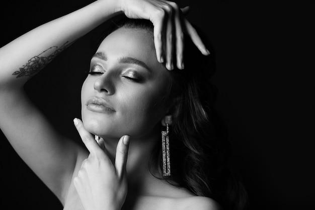 スタジオで影でポーズをとる素敵な若い女性の黒と白の肖像画。空きスペース
