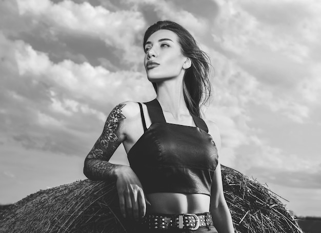 해질녘 건초더미 앞에서 문신을 한 소녀의 흑백 초상화. 혼합 매체