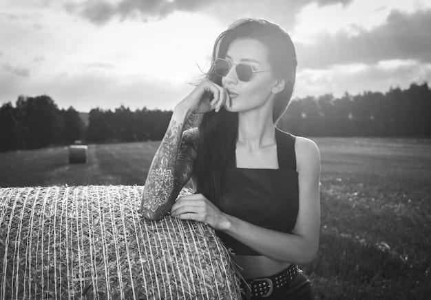 석양에 건초 더미의 배경에 선글라스에 문신을 한 소녀의 흑백 초상화. 혼합 매체