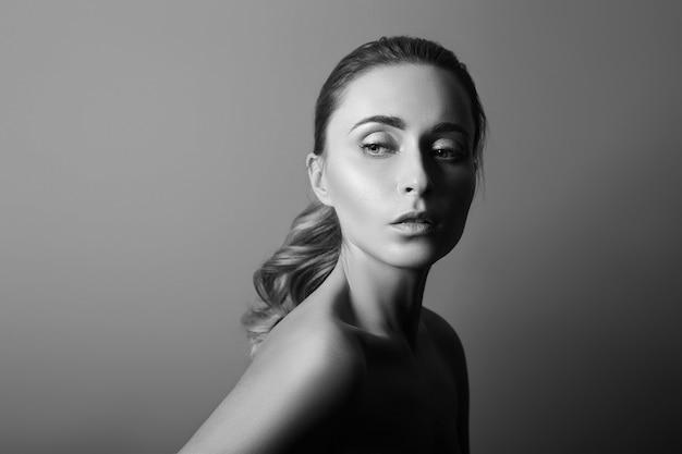 완벽한 깨끗한 피부 클로즈업을 한 여성의 흑백 초상화. 어두운 배경에 아름 다운 갈색 머리