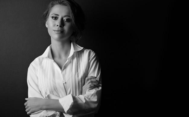 スタジオで影でポーズをとるエレガントな若い女性の黒と白の肖像画。空きスペース