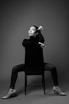Черно-белый портрет азиатской трансгендерной женщины, сидящей