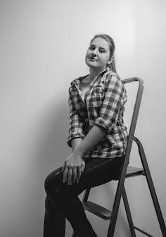 Черно-белый портрет красивой улыбающейся женщины в рубашке, сидящей на лестнице