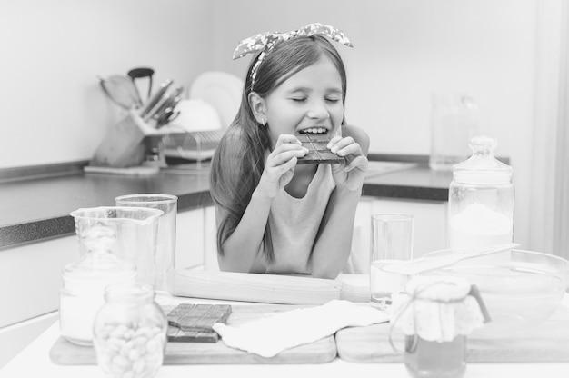 Черно-белый портрет милой девушки, опирающейся на кухонный стол и едящей шоколад