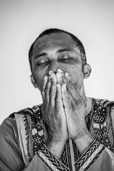 Черно-белый портрет этнического человека, пытаясь контролировать его страдания, стараясь не плакать. плохие эмоции