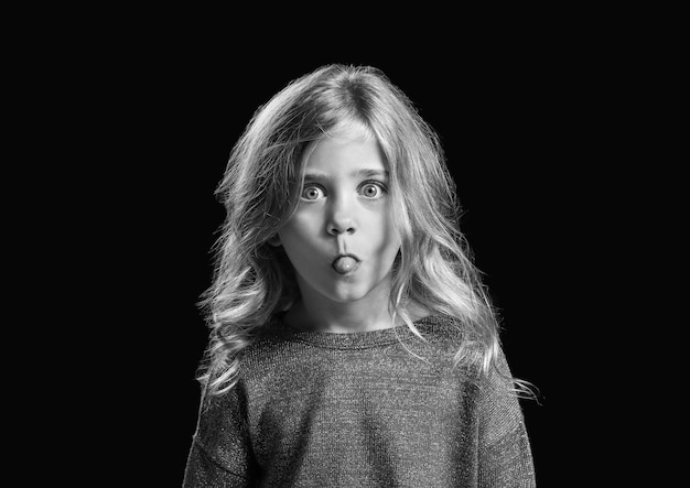 Черно-белый портрет морщинистой маленькой девочки на темноте