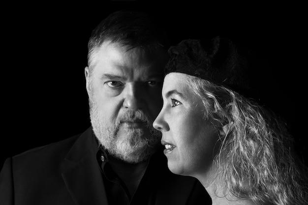 黒の背景にシニア大人のカップルの黒と白の肖像画