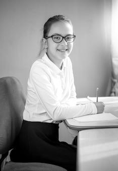Черно-белый портрет улыбающейся школьницы, позирующей за столом в классе