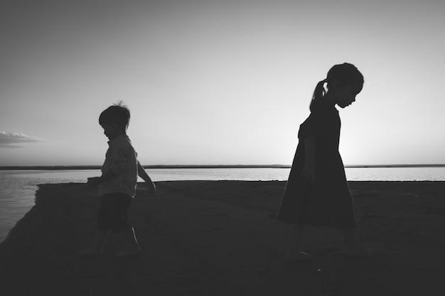 屋外で異なる方向に出発する2人の子供の黒と白の肖像画。