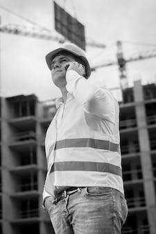 건설 현장에서 전화로 이야기하는 젊은 건설 엔지니어의 흑백 초상화. 배경에 무거운 블록을 들어 올리는 크레인