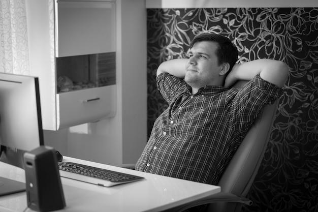休憩中にオフィスで椅子でリラックスした若い男の黒と白の肖像画