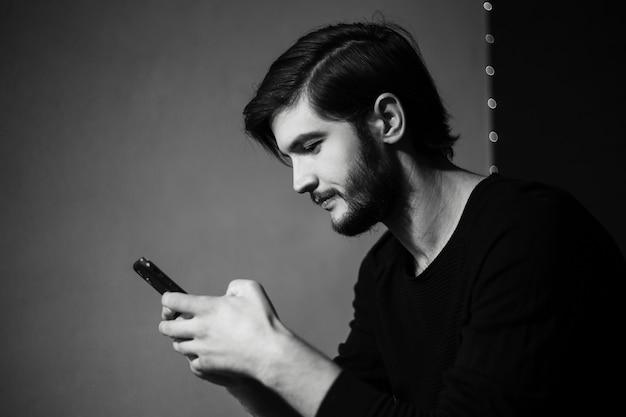 スマートフォンを手に若い男の黒と白の肖像画。