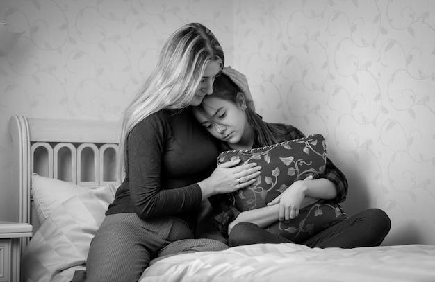 ベッドの上で10代の娘を慰める若い母親の黒と白の肖像画