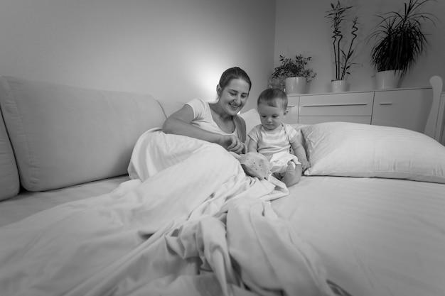 늦은 저녁에 침대에서 아기와 이야기하는 젊은 어머니의 흑백 초상화