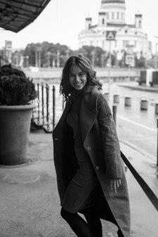 Черно-белый портрет молодой улыбающейся счастливой красивой девушки в пальто, водолазке, позирующей на открытом воздухе