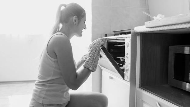 부엌에 있는 오븐에서 맛있는 달콤한 쿠키를 굽고 있는 웃고 있는 젊은 여성의 흑백 초상화