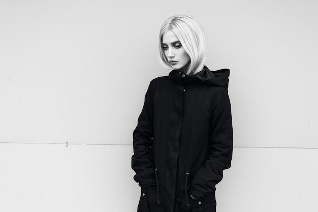 Черно-белый портрет молодой вдумчивой девушки в куртке парка на открытом воздухе.