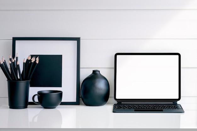 흑인과 백인 reative 작업 영역 개념. 키보드, 연필, 컵 및 흰색 테이블에 나무 프레임 모형 빈 화면 태블릿.