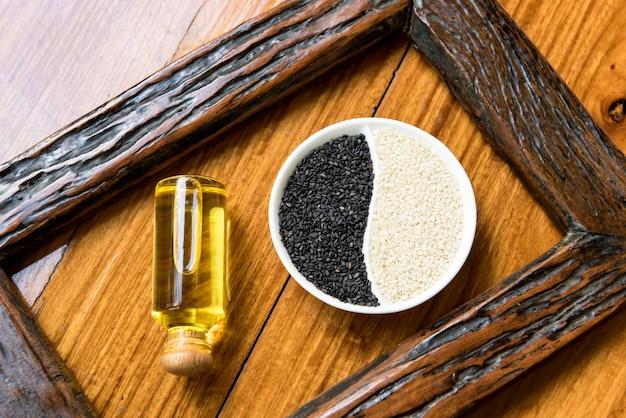 Черно-белые семена кунжута и масло на деревянном столе