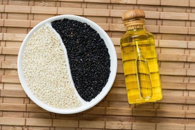 Черно-белые семена кунжута и масло на бамбуковом фоне