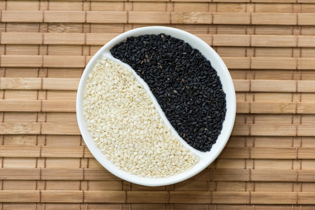 Черно-белые семена кунжута на фоне бамбука