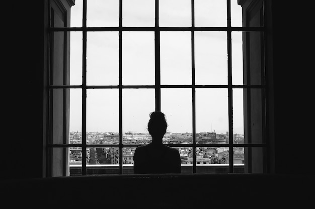 Черно-белый снимок одинокой женщины, стоящей перед окнами и смотрящей на здания