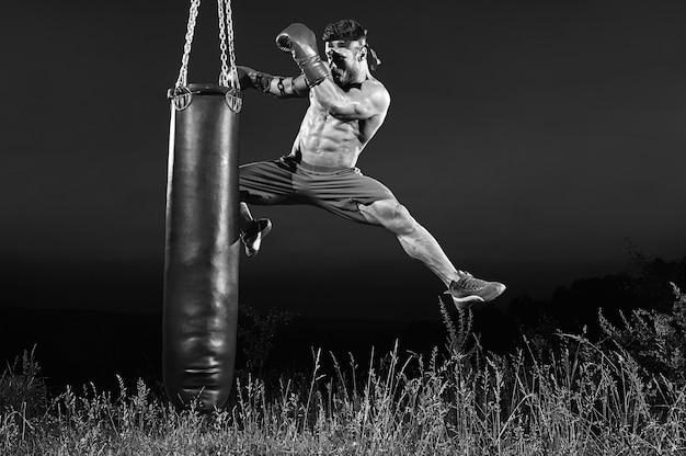 Черно-белый снимок мужского кик-боксера, который прыгает и пинает тяжелую боксерскую грушу, тренируясь на открытом воздухе.